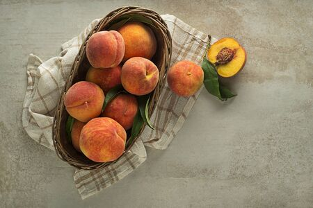 Ripe peaches with leaves in basket on table background