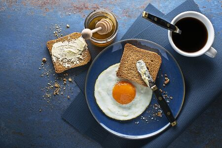 Breakfast of fried egg and bread with honey and butter on table top view. Healthy breakfast food.