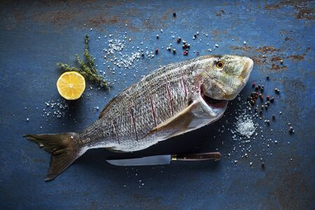 Delicious fresh fish with spices on vintage background. Healthy diet eating or cooking concept