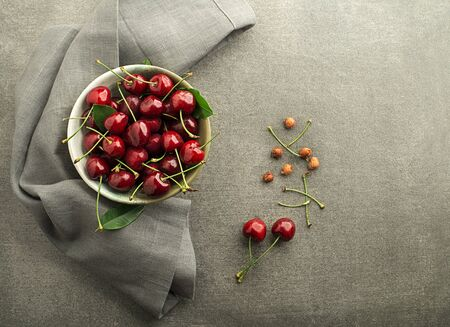 Bowl of fresh red cherries on the table close up