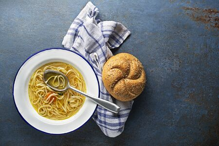 Served hot Hen and Chicken soup with noodles and bread, a place for text. Healthy meal.