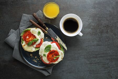 Breakfast served with melted mozzarella sandwich, juice and coffee on the table top view