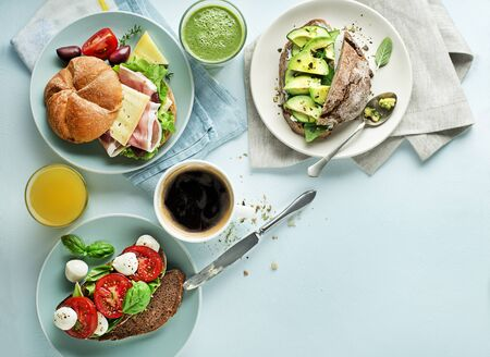 Breakfast served with different sandwiches with vegetable, cheese, ham and drinks.