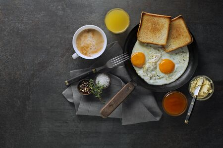Breakfast served with pan of fried eggs, jam, butter, coffee and juice on the table top view.