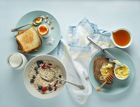 Breakfast served with oatmeal and fruits, boiled egg, honey and butter.