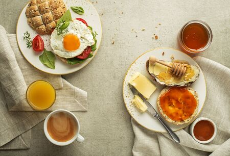 Breakfast served with sandwich with egg, honey with butter and orange juice, coffee.