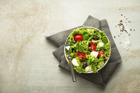 Healthy green salad with tomato and mozzarella cheese.