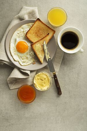 Breakfast served with fried egg, jam, butter, coffee and juice on the table top view.