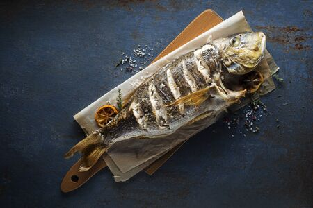 Delicious grilled fish meat with spices and lemon on vintage blue