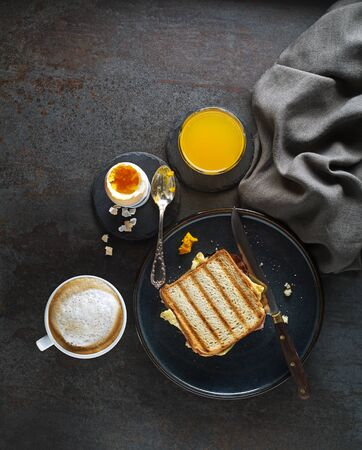 Breakfast served with coffee, juice, toast sandwich and boiled egg.