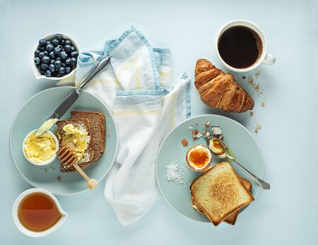 Continental Breakfast meal served with coffee, croissant, egg, bread, honey and butter. Delicious healthy breakfast table.
