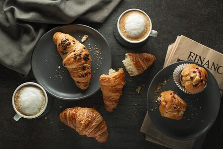 Breakfast served with croissants and coffee. Continental breakfast table with newspaper concept Zdjęcie Seryjne