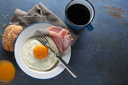 Breakfast meal of ham, fried egg and bread with coffee and juice on table top view. Healthy breakfast food.