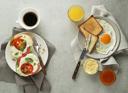 Breakfast buffet served with coffee, juice, jam, butter, fried egg and mozzarella sandwich on grey table top view. Healthy breakfast food.