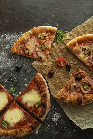 Pizza slices served with mozzarella cheese, ham, mushrooms and tomato sauce