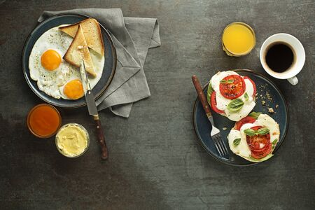 Breakfast buffet served with coffee, juice, jam, butter, fried eggs and mozzarella sandwich on grey table top view. Healthy breakfast food.