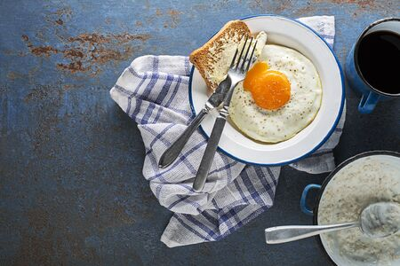 Continental Breakfast meal of fried egg, bread, coffee and oatmeal on table top view. Healthy breakfast tabel.