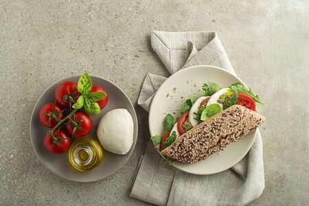 Healthy Sandwich with mozzarella cheese, lettuce, tomato and pesto sauce close up on the table top view. Healthy breakfast food.