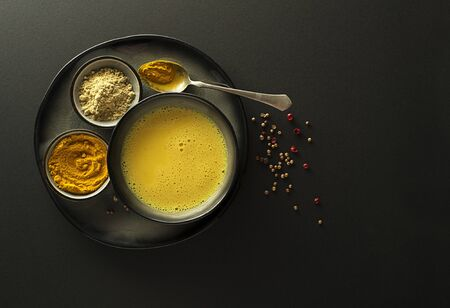 Gesundes Getränk mit Kurkuma und Milch. Goldene Milch, hergestellt mit Kurkuma und anderen Gewürzen