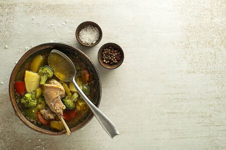 Eating healthy stew with rabbit meat and vegetables on grey background. Zdjęcie Seryjne