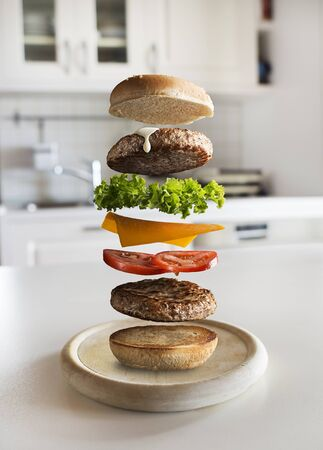Maxi hamburger with flying ingredients placed in the kitchen. Conceptual jumping Burger. Delicious and attractive hamburger with refreshing ingredients