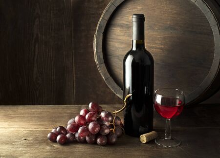 Bottle of selected red wine with barrel on wooden background. Zdjęcie Seryjne