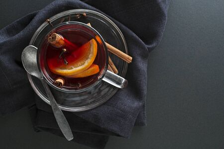 Mulled red wine with spices and fruits on a dark table. Traditional hot drink at Christmas and winter time