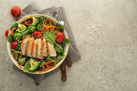 Healthy green salad with chicken breast and fresh vegetables on grey background. Healthy meal.