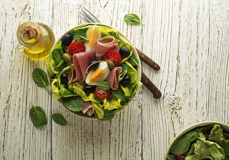 Healthy green salad with prosciutto, egg, olives and tomato on wooden table background. Healthy meal.