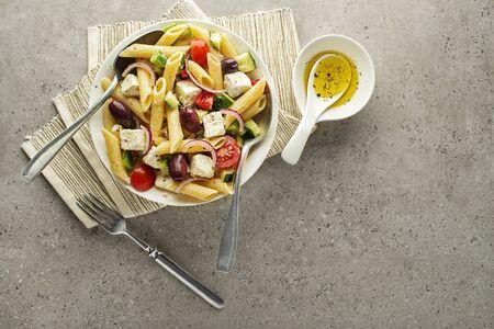Insalata di pasta con formaggio feta e verdure su sfondo grigio. Insalata greca con pasta.
