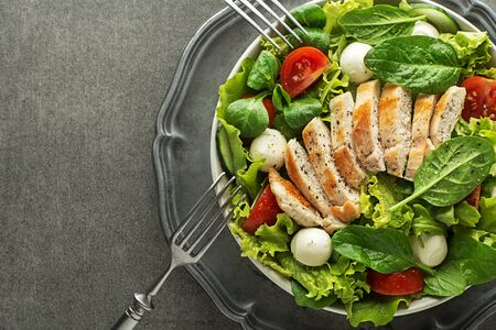 Healthy green salad with chicken breast and mozzarella on grey background