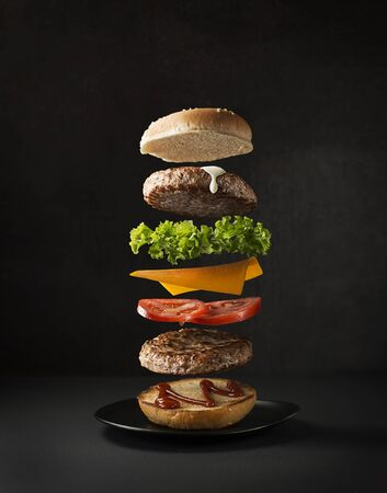 Maxi hamburger with flying ingredients placed on black background. Conceptual jumping Burger. Delicious and attractive hamburger with refreshing ingredients Foto de archivo