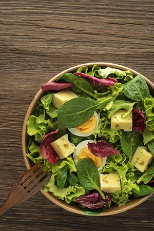 Healthy lettuce salad with eggs and cheese on wooden table background. Healthy meal.
