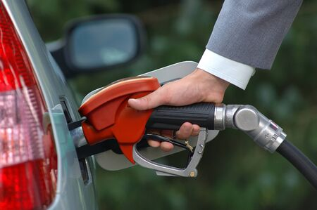 Man pumping petrol with fuel pump. Vehicle fueling facility at petrol station. Petrol price goes down after pandemic coronavirus. low price of fuel. Reklamní fotografie
