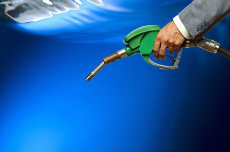 Refueling hose on blue background. Holding green color fuel gasoline dispenser background. Petrol price goes down after pandemic coronavirus. low price of fuel.