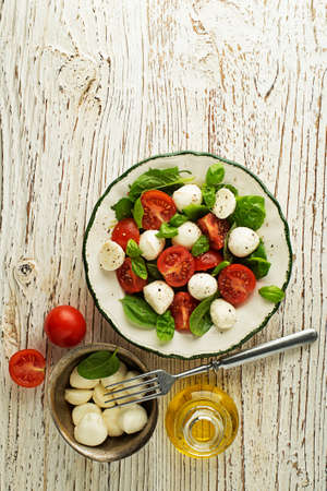 Delicious caprese salad with ripe tomatoes and mozzarella cheese with fresh basil leaves. Italian food. Banque d'images