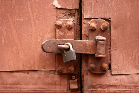 pawl: old  padlock, latch and rusty gate coloured rick-red  Stock Photo
