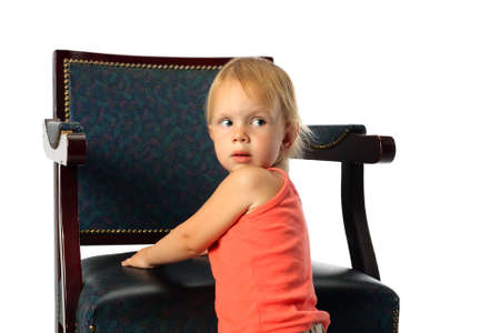 elbowchair: little beauty girl stand near elbow-chair lean its elbows look around and look back Stock Photo