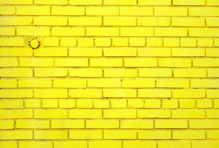 Slightly dusty old brick wall coloured yellow with embedded round closed pipe. photo