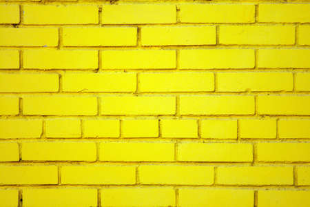 yellow block: Slightly dusty old brick wall coloured yellow with embedded round closed pipe.