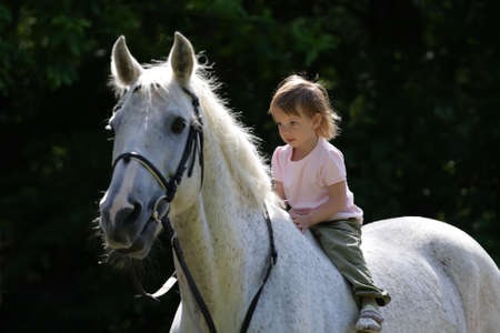 Little beauty intent girl rideing bareback by gray beautiful big horse with black bridle. Animal is not in focus.