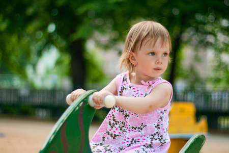 3 persons only: Small thoughtful beauty girl on spring swing. Hot summer.