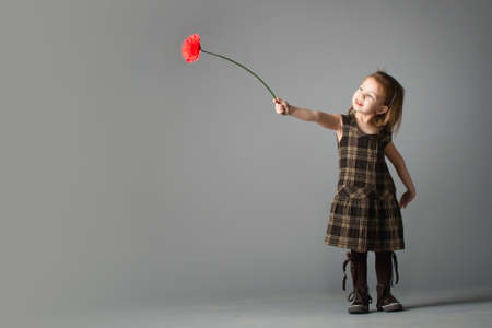 Little beauty girl with red flower. She reach out her's hand with gerbera towards light.