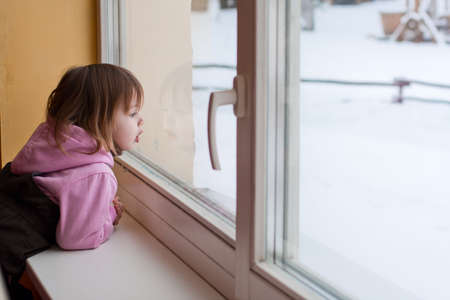 window  glass: Little beauty girl  look out of the window and breathe on the glass so that it grow misted. Winter.