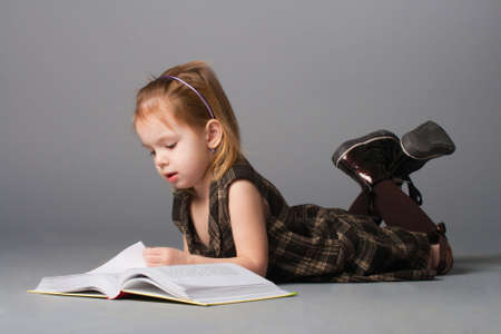 Small beauty girl lying and reading interesting book.  photo