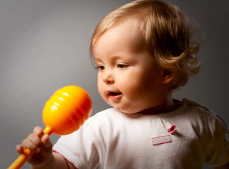 baby facial expressions: Small beauty girl and orange toy microphone. (Soft focus)