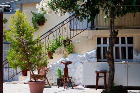 Traditional greek house. White wall, stairs, plants in tubs, window and stool. photo