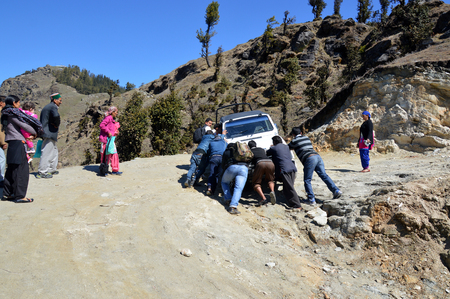 passerby: Passerby pushing a stranded tourist vehicle in an unpaved himalayan road, Shimla, Himachal Pradesh, India.
