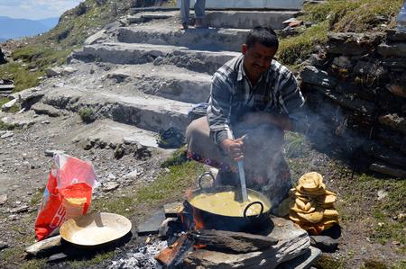 dhoti: A man preparing halwa pooripuri outdoors during tonsuremundan ceremony, Shimla, Himachal Pradesh, India.