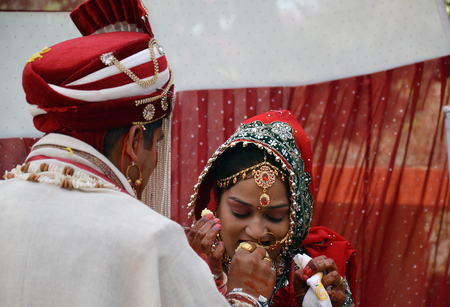 are fed: Bride being fed ladoo(sweet) by groom during varmala ceremony on wedding day.